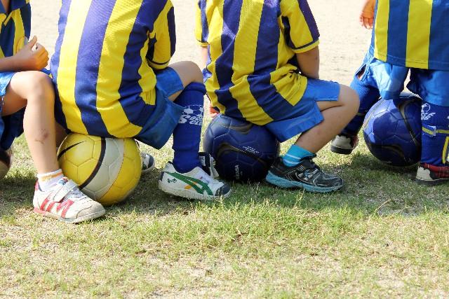 サッカーボールに座る子供