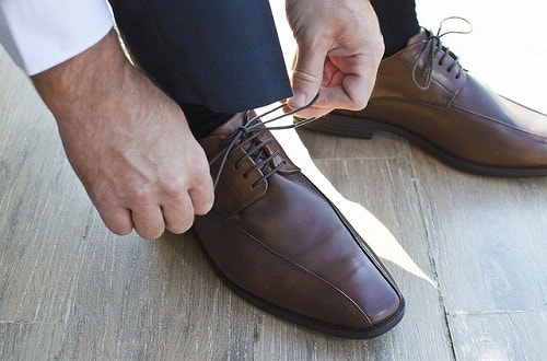 革靴の紐を結ぶ